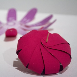 A magenta coloured paper flower, fastened in the shape of a bulb with a toothpick.