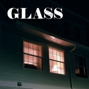"The title ""Glass"" with a shattered ""S"" over a window illuminated in the night."